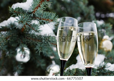 champagne glasses on the background of spruce with toys - stock photo