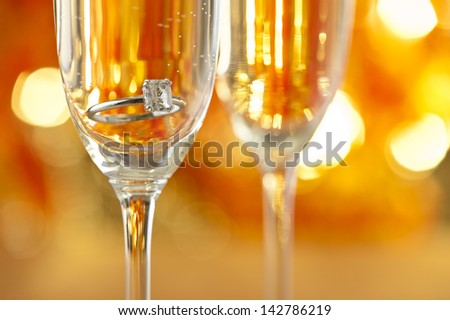 Champagne glasses with engagement Jewelry in front of autumn background