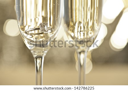 Champagne glasses with engagement Jewelry in front of autumn background - stock photo