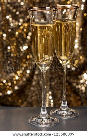 Champagne glasses with submerged ring in front of gold glitter background - stock photo