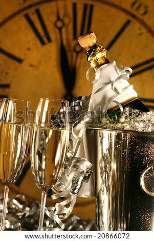 Champagne in bucket with glasses ready for New Years festivities - stock photo