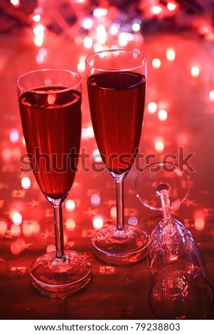 Champagne in glasses and blurred lights on red background - stock photo