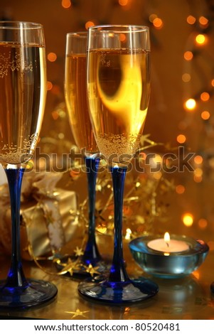 Champagne in glasses and candle light. Lights on golden background.
