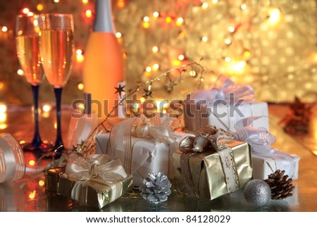 Champagne in glasses and gift boxes on golden background with twinkle lights. - stock photo
