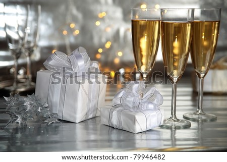Champagne in glasses and gift boxes on sliver background. - stock photo