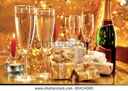 Champagne in glasses and gift boxes. Twinkle lights on background. - stock photo