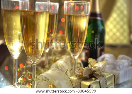 Champagne in glasses and gifts on gold background.