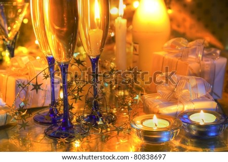 Champagne in glasses,bottle,candle lights,gifts and twinkle light on background.
