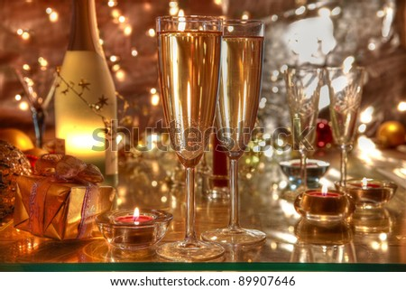 Champagne in glasses, bottle, candle lights on blurred background with lights.