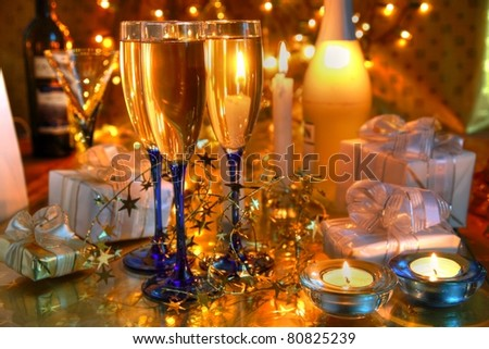 Champagne in glasses,bottle,candles and twinkle lights on golden background.