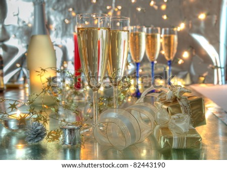 Champagne in glasses,bottle, gift boxes, candles and twinkle lights on background.