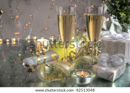 Champagne in glasses,bottle,gifts and twinkle lights on background.