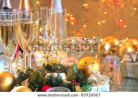 Champagne in glasses,bottles,candle lights,baubles,green twig on background with twinkle lights.