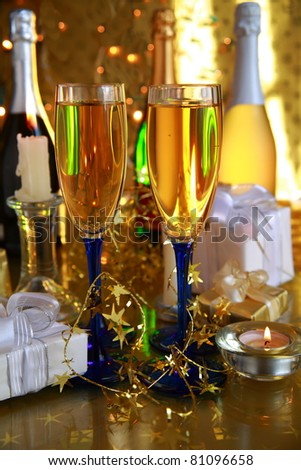 Champagne in glasses,bottles,gift boxes and twinkle lights on gold background.