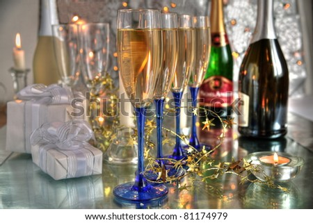 Champagne in glasses,bottles,gifts,candle light on silver background.
