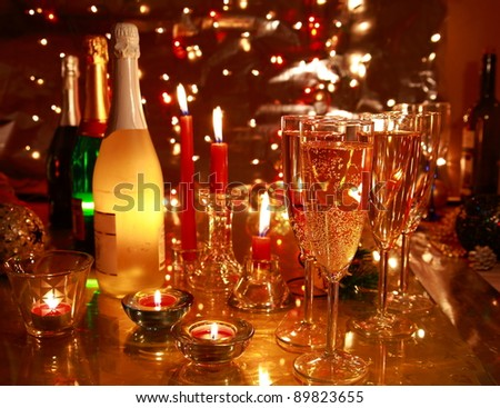 Champagne in glasses,candle lights,bottles and twinkle lights on background.