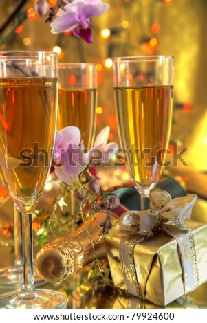 Champagne in glasses,flowers and gift on gold background.