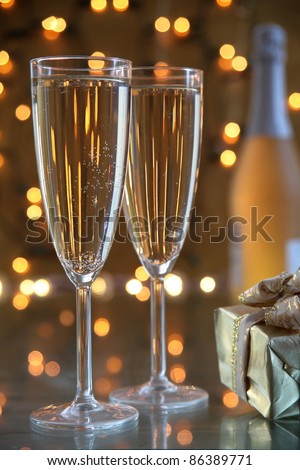 Champagne in glasses,gift box and bottle on background with twinkle lights. - stock photo