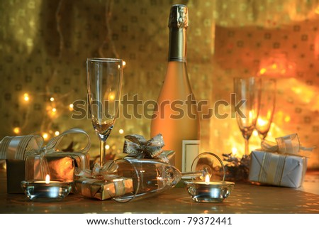 Champagne in glasses,gift boxes,candle lights on gold background.
