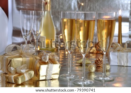 Champagne in glasses, gift boxes on foreground and twinkle lights on silver background. - stock photo
