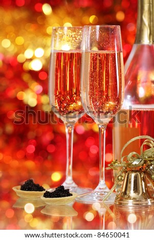 Champagne in two glasses with black caviar at the christmas background - stock photo