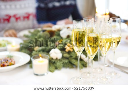 Champagne into a glasses standing on the Christmas table. Close up