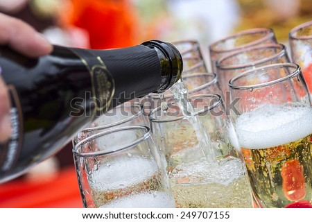 Champagne is poured into glasses - stock photo
