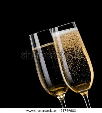 Champagne pouring in to a glass on a black background - stock photo