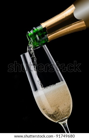 Champagne pouring into a glass on a black background