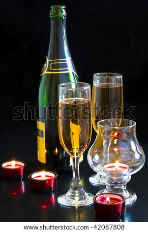 Champagne, red candles in a dark background. - stock photo
