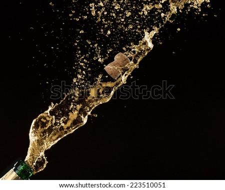 Champagne splashes with cork on black background - stock photo