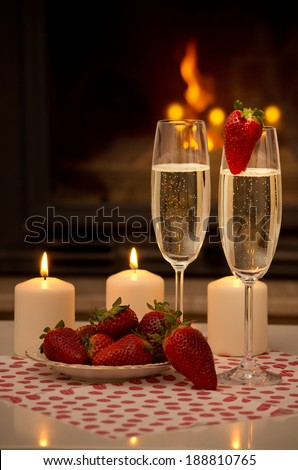 Champagne, strawberries, candles and a romantic evening by the fireplace. - stock photo