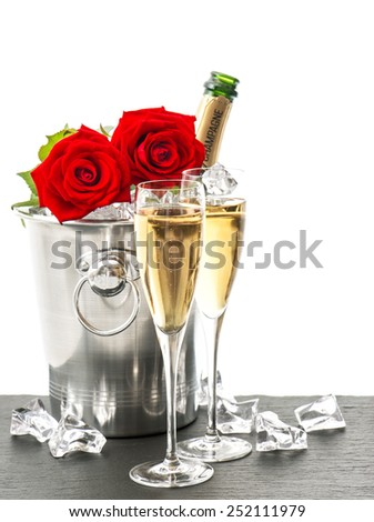 Champagne, two glasses and red roses. Festive arrangement with sparkling wine and flowers - stock photo