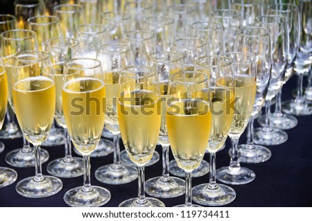 Champagne wine in glasses ready for toasting at wedding reception - stock photo