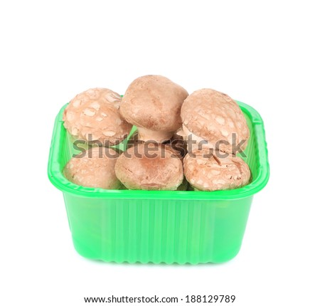 Champignon mushrooms in a green box. Isolated on a white background