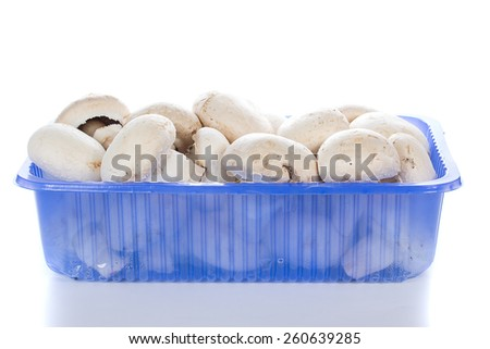 Champignon mushrooms in basket with reflection over white background - stock photo