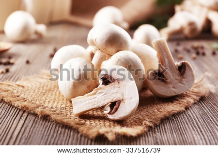 Champignon mushrooms, sacking mat and spices on wooden background - stock photo