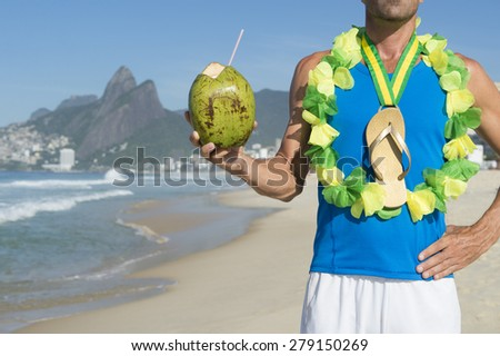 Champion athlete wearing Brazil colors lei around his gold medal flip flop celebrating with coconut on Ipanema Beach Rio de Janeiro Brazil  - stock photo