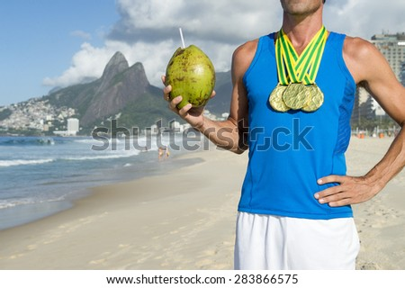 Champion athlete wearing gold medals celebrating with coconut on Ipanema Beach Rio de Janeiro Brazil  - stock photo