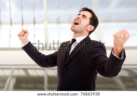 Champion business man standing with fists clenched in victory - stock photo