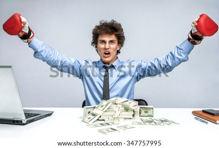 Champion in business, concept sign - angry boxing man. Businessman boxer with a lot of money at the workplace on grey background. High resolution product - stock photo