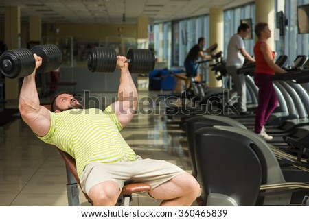 Champion with dumbbells. Sportsman working out in gym. Man doing exercises in gym with dumbbells. People training on the background.