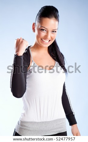 Champion woman standing with fists clenched in victory. Studio shot - stock photo