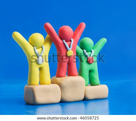Champions made of child's play clay sharing gold, silver and bronze on podium - stock photo