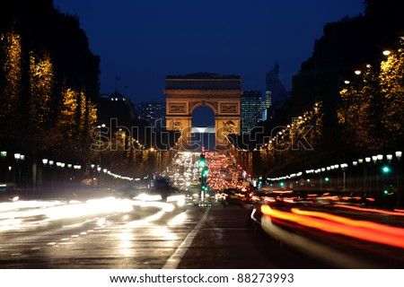Champs-Elysees Avenue with the Arc de Triomphe in Paris France at night - stock photo