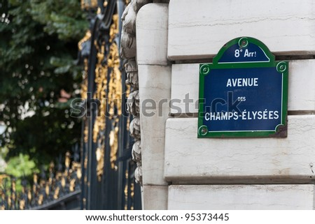 Champs Elysees street sign on a pillar and ornate gate in background