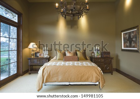 Chandelier hanging over tidy bed at home - stock photo