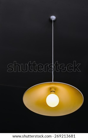 Chandelier with lamp on a dark ceiling. Black Background. - stock photo