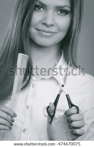 Change of look, new image. Young girl presents comb and scissors. Female stylist preparing equipment to work cut long straight healthy hair.