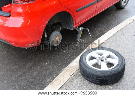 Change wheel in red car - stock photo